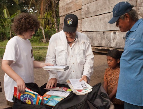 Handing out much needed books and instructional materials to the Village Chief.
