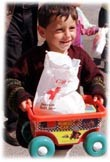 A little boy from Kosovo smiles as he plays with his new toy from the American Red Cross