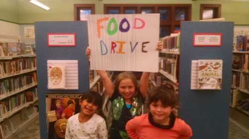 From left to right, 7-year-old Vanessa Noble, 9-year-old Elaina Noble, and 6-year-old Pip Karch, prepare for a food drive.