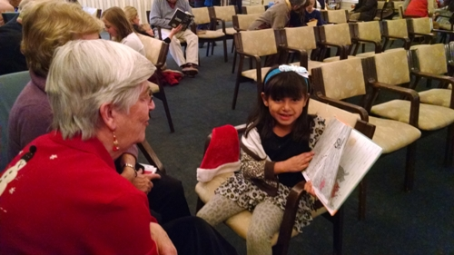 Vanessa reading to the elderly (and putting a smile on their faces) at a holiday party.