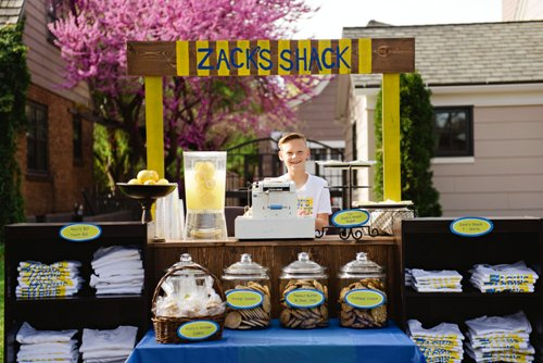 Zack stands proudly at his lemonade and cookie stand, smiling and ready for business.