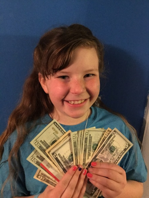 Noelle proudly holds up some of the money she raised.