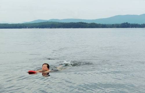 Noelle swims across the lake in order to raise funds for her charity Laps 4 Backs.