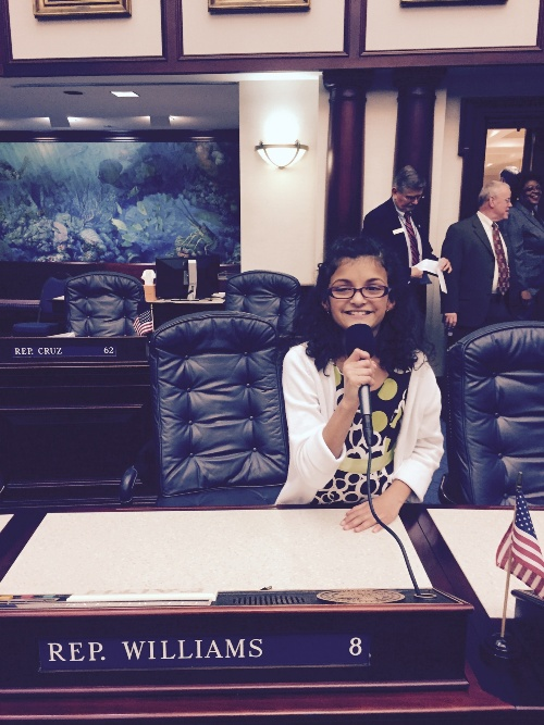 Paloma sits at Representative Williams' chair and practices her speech giving skills.