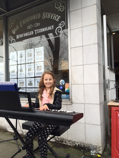 Capri plays piano and sings, smiling happily as she does what she loves most.