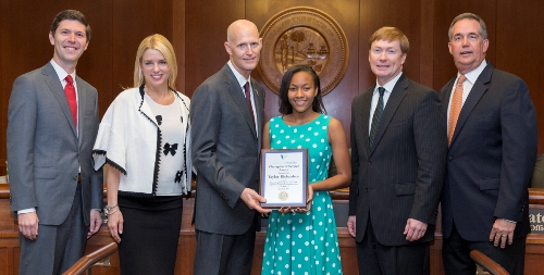 Taylor Richardson receives the Champion of Service award from Florida Governor and staff.