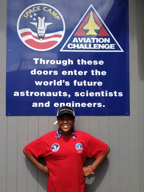 Taylor Richardson stands in front of an Aviation Challenge poster at space camp.