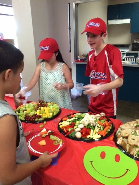 Will Lourcey and other FROGs members serve salad to the hungry.