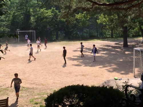 Roll-the-ball: Some boys were playing soccer, while I played football with others